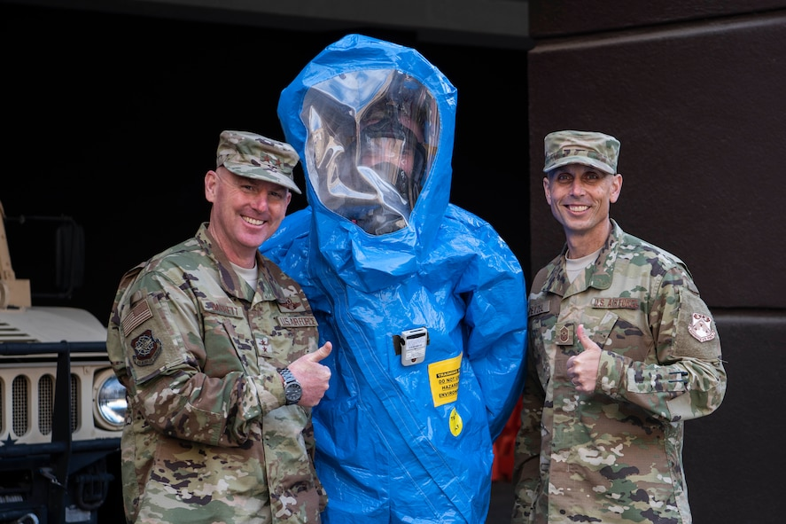 Maj. Gen. Sam Barrett, 18th Air Force commander, and Chief Master Sgt. Todd Petzel, 18th AF command chief, pose for a photo with an Airman from the 375th Medical Group bioenvironmental health technician during a three-day tour Oct. 10 - 13, 2018 at Scott Air Force Base, Illinois. The commander and command chief were able to learn from various Airmen about what they do and how they support the greater mission. (U.S. Air Force photo by Senior Airman Melissa Estevez)