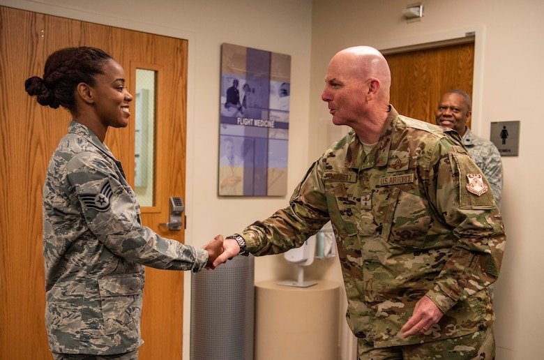 "Maj. Gen. Sam Barrett, 18th Air Force commander, coins Staff Sgt. Jacqueline Lovett, 375th Medical Group, pediatrics clinic flight chief, during a three-day tour Oct. 10 - 13, 2018 at Scott Air Force Base, Illinois. ""Coining"" has been in the military for centuries. It is a way for leaders, to showcase their appreciation for a job well done. (U.S. Air Force photo by Senior Airman Melissa Estevez)"