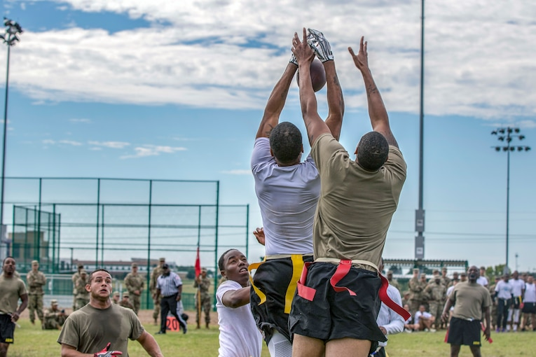 Two soldiers jump to catch a football pass.