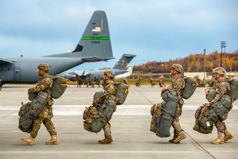 Paratroopers line up outside Air Force aircraft with all their gear.