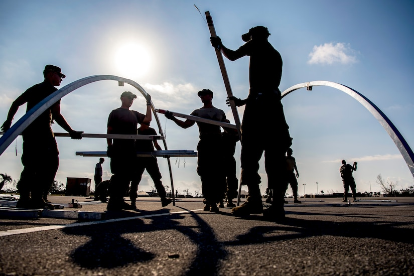 Airmen work together to build a frame for a shelter.
