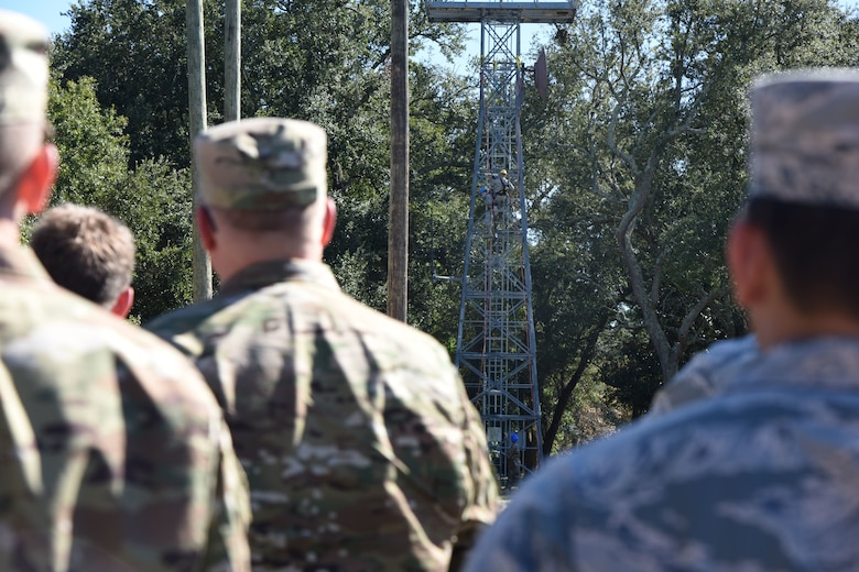 Members of the 85th Engineering Installation Squadron conduct a tower rescue demonstration during the 85th EIS open house outside of Maltby Hall at Keesler Air Force Base, Mississippi, Oct. 11, 2018. Tower rescue and fiber splicing demonstrations were conducted as well as tours inside the tool cage, telecommunications lab and the electromagnetic lab.  (U.S. Air Force photo by Kemberly Groue)