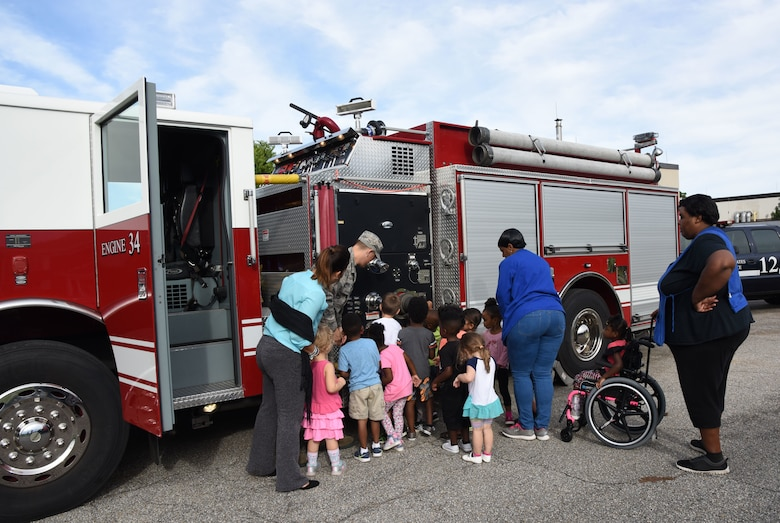 Keesler Child Development Center children receive a tour of a a fire truck during Fire Prevention Week outside of the CDC on Keesler Air Force Base, Mississippi, Oct. 10, 2018. The week-long event included fire drills, literature hand-outs and stove fire demonstrations around the base and concluded with an open house at the fire department Oct. 13. (U.S. Air Force photo by Kemberly Groue)