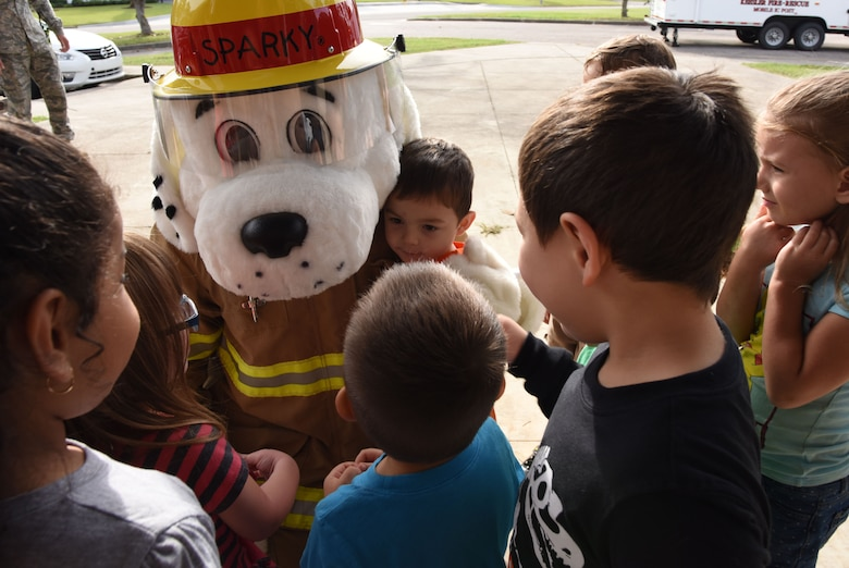 Sparky, the Fire Dog, visits children at the Child Development Center during Fire Prevention Week on Keesler Air Force Base, Mississippi, Oct. 10, 2018. The week-long event included fire drills, literature hand-outs and stove fire demonstrations around the base and concluded with an open house at the fire department Oct. 13. (U.S. Air Force photo by Kemberly Groue)