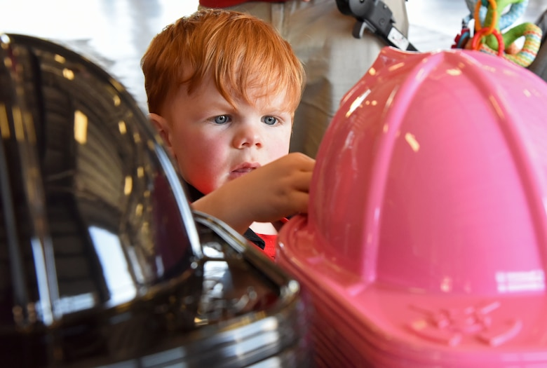 Brayden Pettus, son of James Pettus, 81st Infrastructure Division firefighter, selects a fire hat during a open house at the fire station at Keesler Air Force Base, Mississippi, Oct. 13, 2018. Keesler ended its Fire Prevention Week celebration with  an open house which consisted of displays, fire truck rides and fire prevention demonstrations. (U.S. Air Force photo by Kemberly Groue)