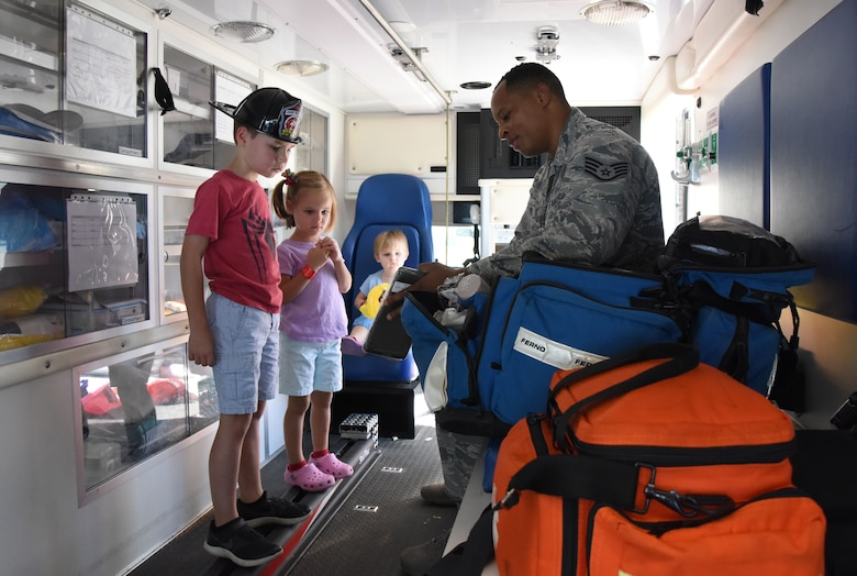 U.S. Air Force Staff Sgt. Andre White, 81st Medical Operations Squadron medical technician, speak to children about ambulance medical contents during a open house at the fire station at Keesler Air Force Base, Mississippi, Oct. 13, 2018. Keesler celebrated Fire Prevention Week by conducting random fire drills, visiting various facilities with Sparky the Fire Dog, and conducting an open house at the fire department while providing stove and fire extinguisher demonstrations. (U.S. Air Force photo by Kemberly Groue)