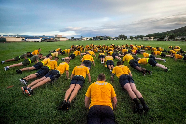Service members in yellow shirts and blue shorts do pushups in a circle on a grass field.