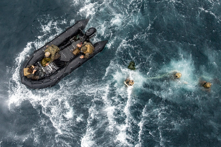 Seen from above, marines swim toward a rubber boat in the open ocean.