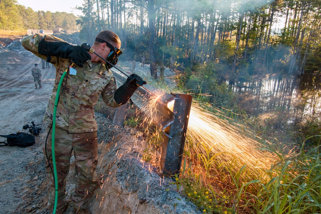 A soldier cuts through  guardrail and sprays sparks evenywhere.