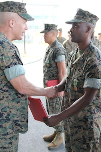 USAG CAMP HUMPHREYS, Republic of Korea – Maj. Gen. Patrick J. Hermesmann (left), commander of U.S. Marine Corps Forces Korea, awards Petty Officer 1st Class Andre Cooper, head medical representative for MARFORK, a Navy and Marine Corps Achievement Medal here, Oct. 4. MARFORK awarded Cooper for his contributions to the unit, which ensured their readiness to support the mission. (U.S. Marine Corps photo by Staff Sgt. Anthony Kirby/Released)