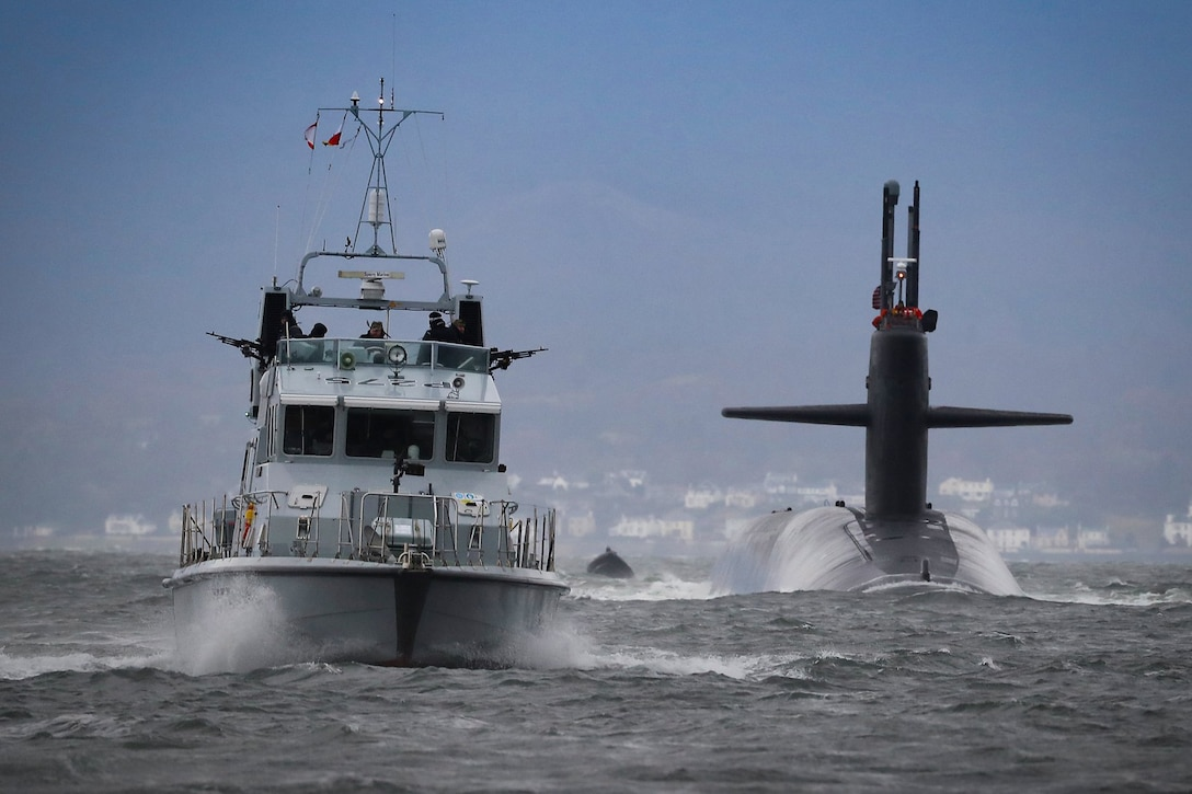 A submarine and boat drive past one another.
