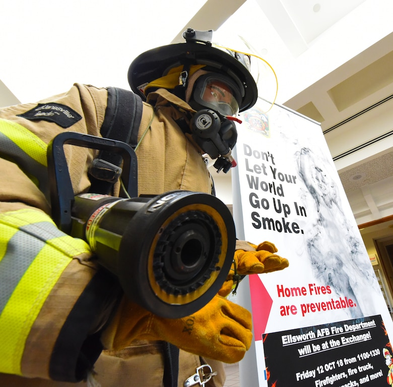 A training dummy dressed like a firefighter stands next to a fire prevention poster at the Exchange on Ellsworth Air Force Base, S.D., Oct. 10, 2018. The 28th Civil Engineer Squadron fire protection flight hosted events, such as a firefighter challenge, a parade and fire safety demonstrations, at Ellsworth AFB and in Box Elder during National Fire Prevention and Safety Week. (U.S. Air Force photo by Airman 1st Class Thomas Karol)