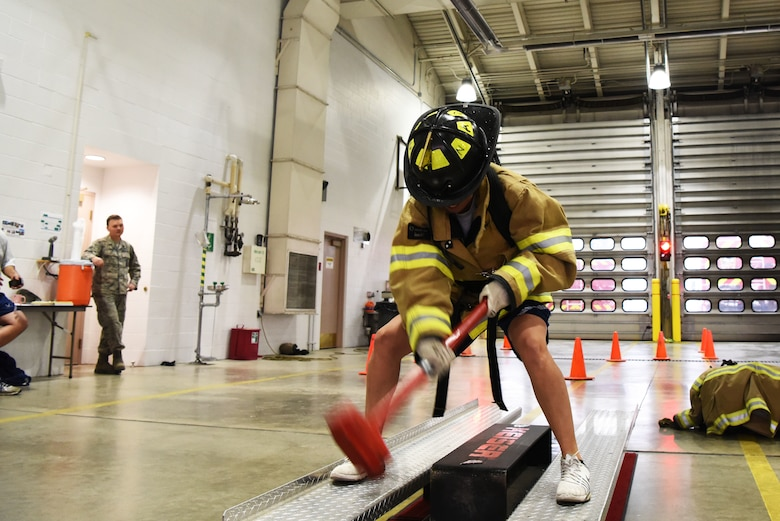 Senior Airman Caitlyn Halloway, a 28th Logistics Readiness Squadron vehicle maintenance technician, hits the Kaiser I-beam of a FORCE Machine with a sledgehammer during the Firefighter Challenge at Ellsworth Air Force Base, S.D., Oct. 5, 2018. The 28th Civil Engineer Squadron fire protection flight hosted multiple events during National Fire Prevention and Safety Week, including the Firefighter Challenge, a parade and school demonstrations. (U.S. Air Force photo by Airman 1st Class Thomas Karol)
