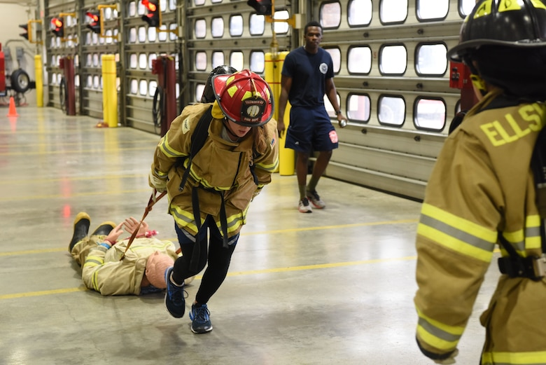Capt. Saira McGan, a 28th Logistics Readiness Squadron operations officer, pulls a training dummy while racing through the Firefighter Challenge at Ellsworth Air Force Base, S.D., Oct. 5, 2018. The 28th Civil Engineer Squadron fire protection flight hosted multiple events during National Fire Prevention and Safety Week, including a Firefighter Challenge, a parade and school demonstrations. (U.S. Air Force photo by Airman 1st Class Thomas Karol)