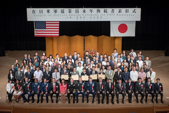 Award winners and distinguished guests pose for a photo at the conclusion of the United States Forces Japan Length-of-Service Awards Ceremony at the Yutorogi Hall in Hamura City, Japan, Oct. 10, 2018.