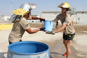 Tech. Sgt. Carlos Oteroflores, hands a bucket of water to Airman 1st Class Christopher Swanson, both assigned to the 380th Aircraft Maintenance Squadron, during the bucket brigade event of the Fire Muster Competition, Oct. 7, 2018 at Al Dhafra Air Base, United Arab Emirates. The bucket brigade was a throwback to the old days when a town would work together to put out building fires by using buckets. (U.S. Air Force photo by Tech. Sgt. Darnell T. Cannady)