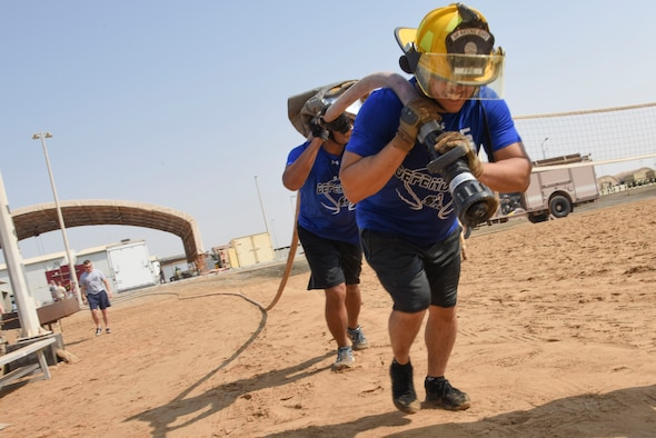 Tech. Sgt. Alexander Bombita and Senior Airman Engel Placencia-Valdez, both assigned to the 380th Expeditionary Security Forces Squadron, pull a charged fire hose during the Fire Muster Competition, Oct. 7, 2018 at Al Dhafra Air Base, United Arab Emirates. This event allowed two-person teams to compete in various challenges to experience what it is like to be a fire fighter. (U.S. Air Force photo by Tech. Sgt. Darnell T. Cannady)
