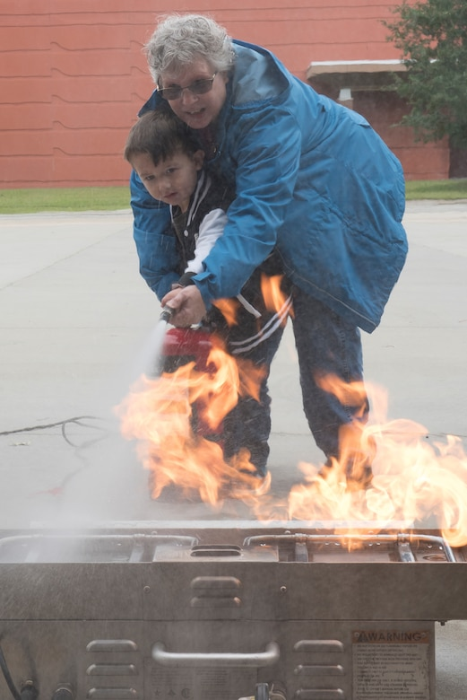 John Henry Yohn, age 3, son of Brian Yohn, Fort Eustis Fire and Emergency Services firefighter, and his grandmother, Sheryl Yohn, put out a fire with an extinguisher during the Fort Eustis Fire and Emergency Services Open House event at Joint Base Langley-Eustis, Va., Oct. 13, 2018.
