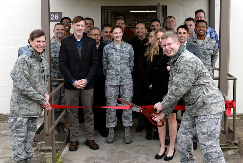 Members of the 346th Test Squadron, Unified Capabilities Assessment Program team cut the ribbon during a ceremony at Joint Base San Antonio-Lackland Medina Annex, Texas, Oct. 15, 2018. The ceremony was hosted to welcome the UCAP team to its new home. The team provides Department of Defense Information Network Approved Products List testing of communications equipment before the equipment can be connected to the DODIN. UCAP is the only Air Force lab that provides DODIN APL testing and results are accepted DOD-wide. (U.S. Air Force photo by Tech. Sgt. R.J. Biermann)