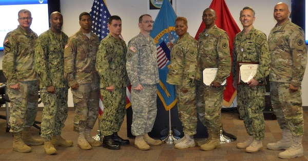 DLA Troop Support Commander Army Brig. Gen. Mark Simerly (far left) and DLA Troop Support Joint Reserve Force team lead Army Col. James Gill (far right) pose with JRF members who were recognized for excellence at a town hall Oct. 12 in Philadelphia.