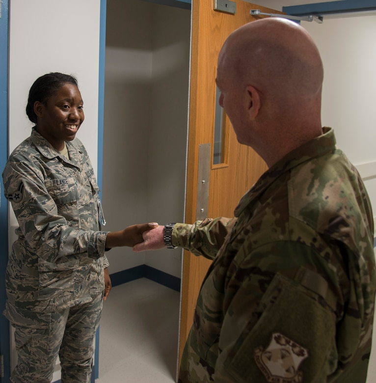Maj. Gen. Sam Barrett, 18th Air Force commander, coins Dominique Lance, 375th Medical Support Squadron medical material technician, during his visit to the 375th Medical Group on Oct. 11, 2018, at Scott Air Force Base, Illinois. (U.S. Air Force photo by Airman 1st Class Nathaniel Hudson)