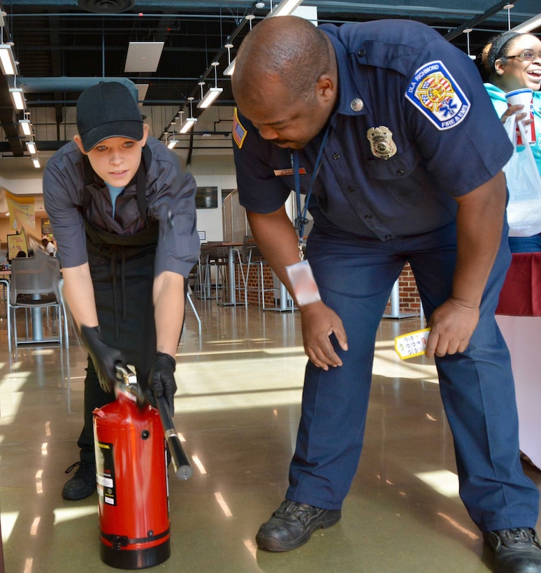 firefighter gives food service worker fire extinguisher training