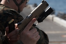 A reconnaissance Marine with the 31st Marine Expeditionary Unit's Amphibious Reconnaissance Platoon reloads an M1911 .45-caliber pistol aboard the flight deck of the amphibious assault ship USS Wasp, underway in the East China Sea, Oct. 15, 2018. The 31st MEU, the Marine Corps' only continuously forward-deployed MEU, provides a flexible force ready to perform a wide range of military operations.