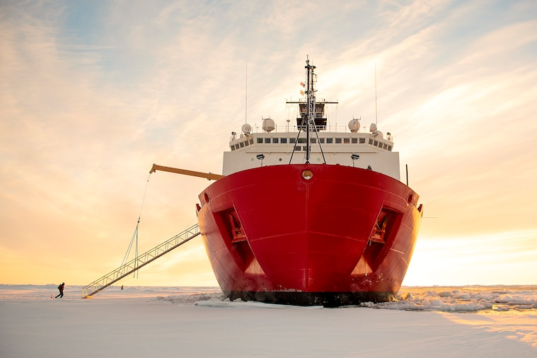 A person approaches a giant red ship sitting on an ice field against a pink-streaked sky.