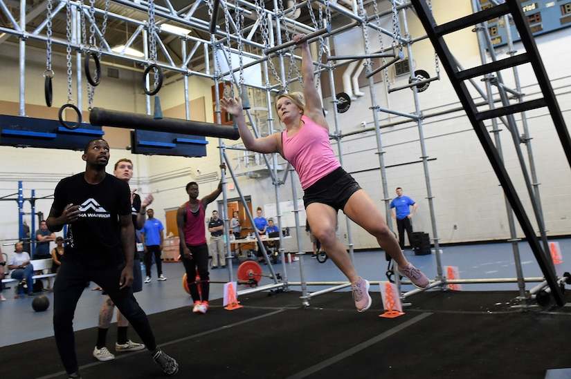 """2nd Lt. Darby Germain, a section commander assigned to the 628th Force Support Squadron, swings across the """"broken bars"""" during the Alpha Warrior regional competition Oct. 13, 2018, at Joint Base Charleston, S.C."""