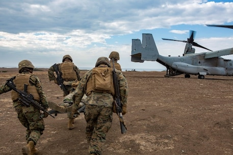 U.S. Marines with Service Company, 9th Communications Battalion, I Marine Expeditionary Force Information Group, run to an MV-22B Osprey as they execute an air casualty evacuation drill at Marine Corps Base Camp Pendleton, Oct. 2, 2018. The drill was part of a field exercise the battalion executed providing the Marines realistic combat training. (U.S. Marine Corps photo by Cpl. Cutler Brice.)