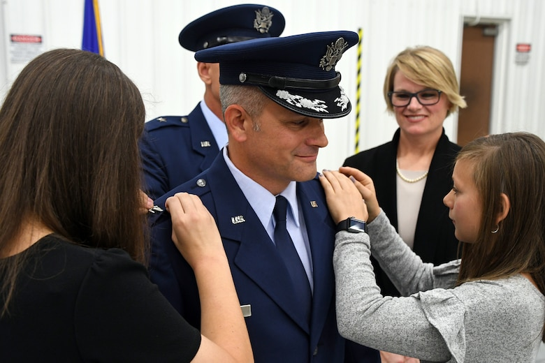 Family members of Col. Brad Douglass help pin the colonel rank on his dress uniform during a promotion and assumption of command ceremony held Oct. 13, 2018 at Dobbins Air Reserve Base, Ga. Most recently, he held an Individual Mobilization Augmentee position at the Pentagon where he worked with the A4 Nuclear Weapons, Missiles and Munitions Division. (U.S. Air Force photo/Senior Airman Josh Kincaid)