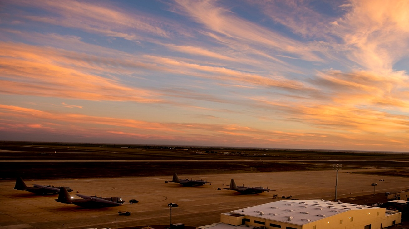 Planes sit on the Cannon Air Force Base flight line as the sun sets