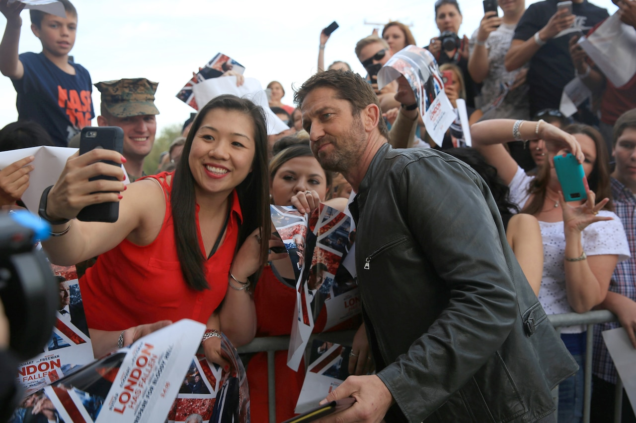 Movie star Gerard Butler takes a selfie with a woman.
