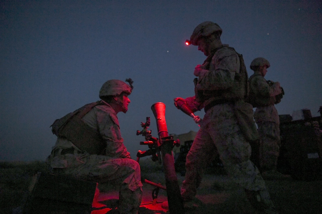 Marines wait for the order to fire a mortar at night.
