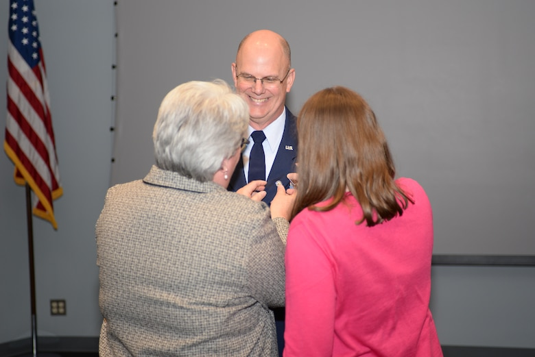 Col. John C. Greenan, receives his retirement pin from his wife and daughter during his retirement ceremony, Oct. 13, 2018 at Pease Air National Guard Base, N.H. Photo by Staff Sgt. Ashlyn J. Correia/ N.H. Air National Guard.
