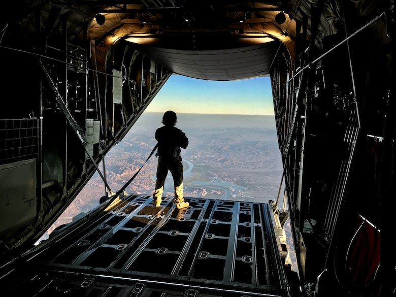 Senior Airman Christopher Godkin, 815th Airlift Squadron loadmaster, looks out the cargo door at 9,000 feet over Laguna Army Airfield at Yuma Army Proving Grounds, Yuma, Ariz during a combined training event with the Military Freefall School, Oct. 1-5, 2018.  The Air Force Reserve 815th AS provided airlift for the joint forces training school, which covers all aspects of military freefall parachuting. (U.S. Air Force photo by Master Sgt. Anthony Flores)