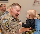 U.S. Army Staff Sgt. Corey Showalter of the 156th Military Police Law and Order Detachment greets his child after returning to Charleston, West Virginia Oct. 10, 2018 following a nine month deployment to Afghanistan. (West Virginia National Guard photo by Bo Wriston)