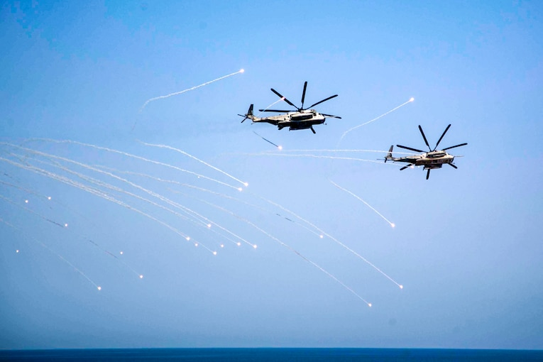 Two helicopters fly between flares over open water.