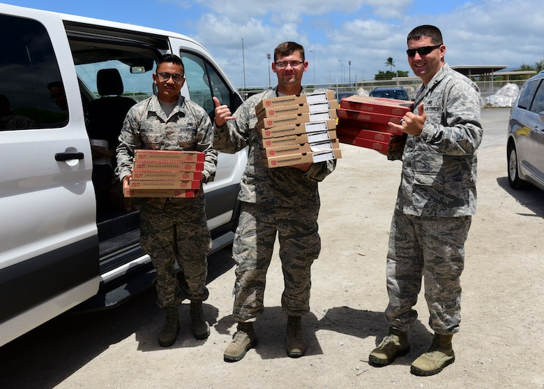 U.S. Air Force Chaplain (Capt.) Jonathan Ayers, the 509th Maintenance Group chaplain, right, helps Senior Airman Dalton Deleon and Tech. Sgt. David Maskowski, deliver pizza to maintenance Airmen during U.S. Strategic Command's Bomber Task Force deployment to Joint Base Pearl Harbor-Hickam, Hawaii, Sept. 6, 2018. During a few weeks of the six-week deployment, the program sponsored a two-person Religious Support Team to ensure the 200 Airmen deployed there from Whiteman were spiritually and emotionally fit to accomplish their mission. (U.S. Air Force photo by Staff Sgt. Danielle Quilla)