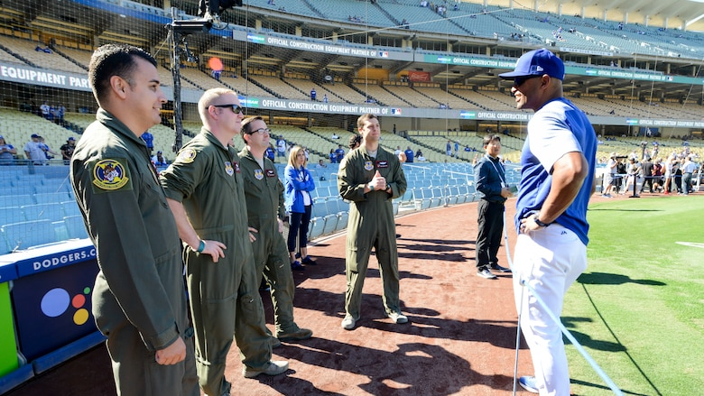 Tech. Sgt. Robert Villa, Master Sgt. Caleb Patterson, Maj. Duncan Reed and Maj. Dan Edelstein, all with 418th Flight Test Squadron, 412th Test Wing, talks with Los Angeles Dodgers first base coach George Lombard prior to Game 3 of Major League Baseball's National League Championship Series between the Los Angeles Dodgers and Milwaukee Brewers at Dodger Stadium in Los Angeles, California, Oct. 15. (U.S. Air Force photo by Giancarlo Casem)