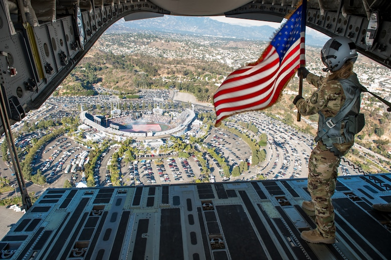Staff Sgt. Kori Myers, 418th Flight Test Squadron load master, waves the American flag out of the back of a C-17 Globemaster III during the beginning of Game 3 of the National League Championship Series between the L.A. Dodgers and Milwaukee Brewers. The 412th Test Wing at Edwards Air Force Base, California, provided the C-17 for the ceremonial flyover. (U.S. Air Force photo by Kyle Larson)