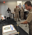 IMAGE: DAHLGREN, Va. (Oct. 12, 2018) - Lt. Adam Mattison cuts the cake in celebration of the Navy's 243rd birthday at Naval Surface Warfare Center Dahlgren Division (NSWCDD). The event featured Mattison as the command's youngest 