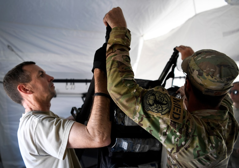 (From left) Col. Brendan Noone and Tech. Sgt. Daniel Green, 96th Medical Group flight surgeon and medical technician, Moody Air Force Base, Georgia, hang medical supplies at Tyndall Air Force Base, Florida, Oct. 15, 2018. Members from Moody Air Force Base travelled down to support standing up an operational medical facility after Hurricane Michael devastated the base. (U.S. Air Force photo by SSgt Matthew Lotz)