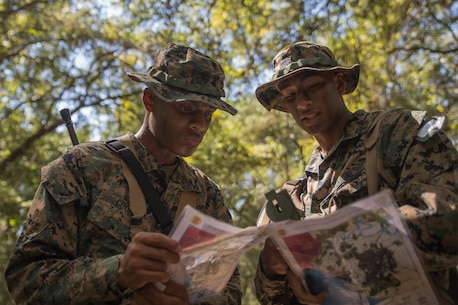 Recruits with Mike Company, 3rd Recruit Training Battalion, examine and plot points on their maps during the land navigation course at Elliot's Beach on Marine Corps Recruit Depot, Parris Island, S.C., Oct. 04, 2018. The Land Navigation Course teaches recruits how to properly navigate unfamiliar terrain. (U.S. Marine Corps photo by Cpl. Vivien Alstad)