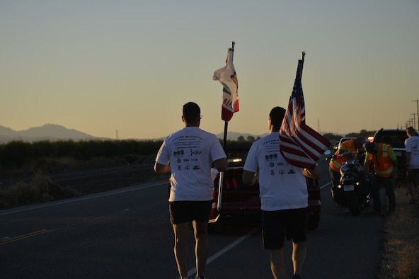 Two members of the 7th Annual California Run for the Fallen Honor Run team carry the U.S. and California flags as they run through Lodi, Calif., Oct. 13, 2018. The event consists of a 150-mile run through 23 towns. At every mile, runners placed American flags, known as 'hero markers,' in the ground to honor California service members who made the ultimate sacrifice since 9/11. (Courtesy Photo)