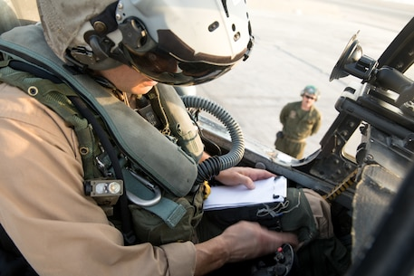 UNDISCLOSED LOCATION, SOUTHWEST ASIA -- U.S. Marine Corps Maj. Scott Symons, a pilot of an F/A-18 Hornet assigned to Marine Fighter Attack Squadron 115, Marine Aircraft Group 31, 2nd Marine Aircraft Wing, prepares his notepad prior to takeoff. The pilots of the F/A-18 provide aerial security for the Marines on the ground while providing a close air support for the Special Purpose Marine Air-Ground Task Force, Crisis Response-Central Command. (U.S. Marine Corps photo by Cpl. Roderick Jacquote)