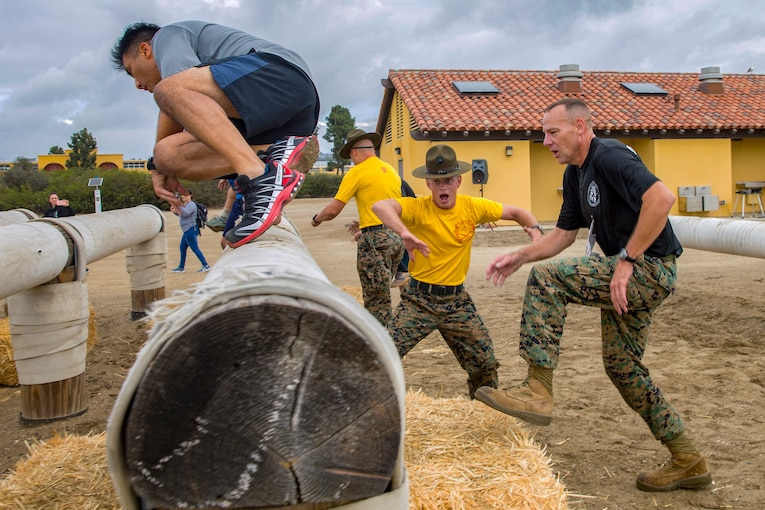 Two participants climb log and hay obstacles while being encouraged by Marine Corps Drill Sergeants.