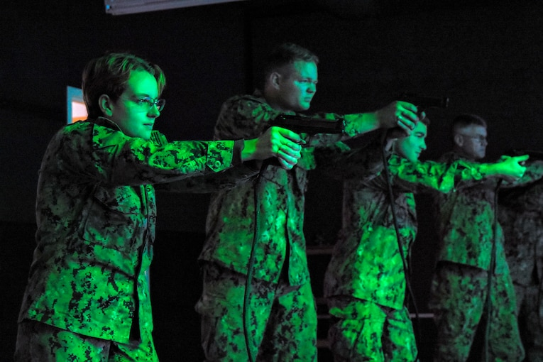 Four sailors in a line aim down pistol sights.