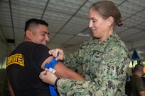 A U.S. Navy doctor  participates in a tourniquet application drill as part of a subject matter expert exchange with Salvadoran military professionals.