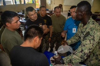 A Salvadoran military professional participates in a cricothyroidotomy application subject matter expert exchange